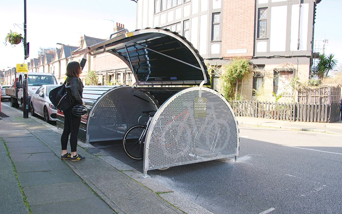 Woman putting her bike into a Cyclehangar on a residential street.