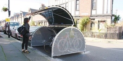 Woman closing the lid for a bikehangar on a residential street