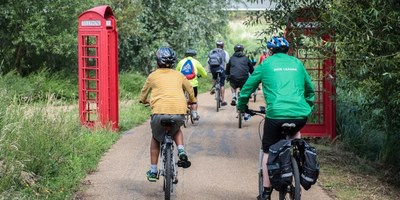 Group cycling through a forest between some red telephone boxes