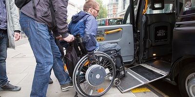 Man boarding taxi using wheelchair ramp