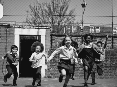 Black and white photo of school children running across a playground