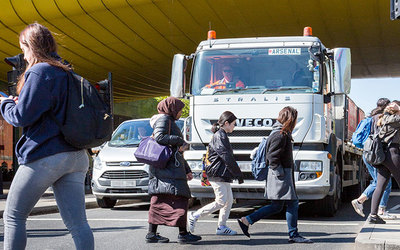 Intersection with pedestrians crossing safely in front of a heavy goods vehicle